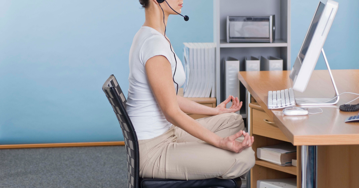 Woman in yoga pose at her desk. Stay healthy while working from home.