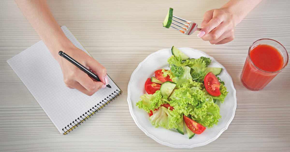 Woman writing out a meal plan while eating salad. How to Set a Healthy Weight Loss Goal - My Fit Habits