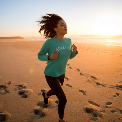 Woman running on the beach, working on weight loss through exercise. My Fit Habits